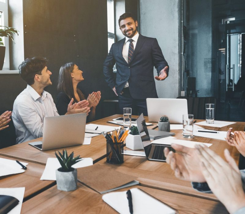 Business presentation. Group of businesspeople clapping hands at meeting in office