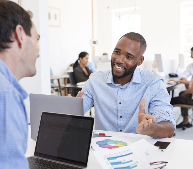 Two men discussing business in a busy office